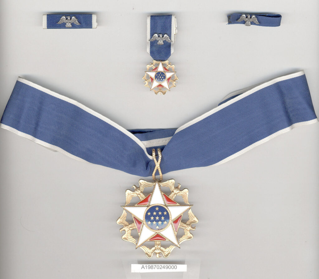 Presidential Medal of Freedom presented to Gen. Charles Yeager; five gold eagles surround white enamel 5 point star with red enamel pentagonal background, blue enamel center disc with 13 white stars. Photo courtesy National Air and Space Museum
